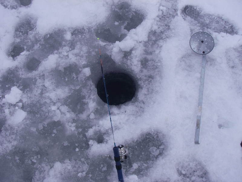 Montana winter ice fishing drilling a hole with an auger to fish