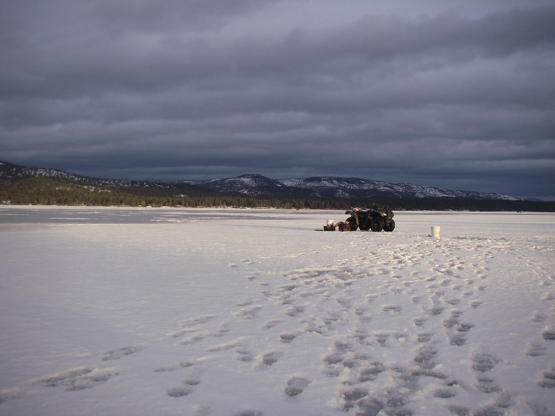 Montana winter ice fishing four wheeler pulling sled on ice