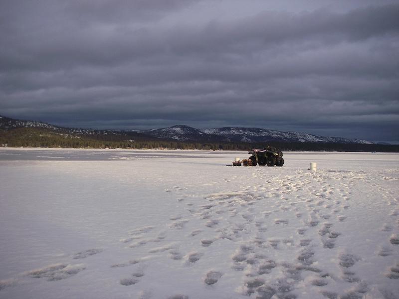 Montana winter ice fishing four wheeler pulling sled on ice