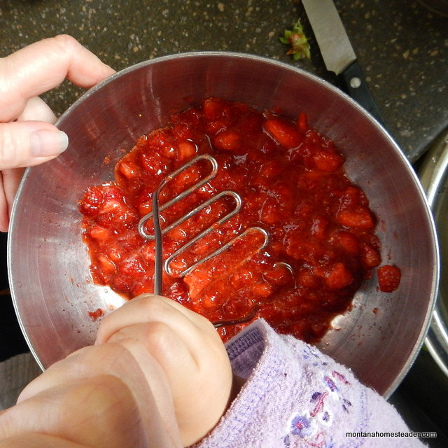 using a potato masher to smash strawberries for honey sweetened no cook strawberry freezer jam