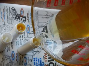Pouring homemade lip balm into tubes with an easy DIY recipe